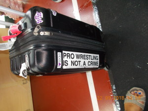 """Nella foto, in alto: la scritta adesiva sulla valigia di Holidead. """"Il wrestling professionale non è un crimine"""""""