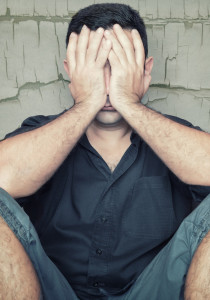 Depressed young man sitting on the floor and covering his face with a grunge wall background