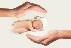 le mani cercano di proteggere un neonato