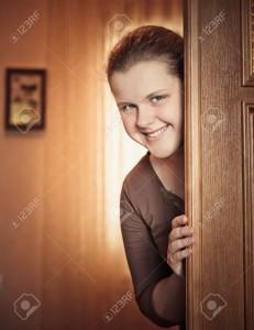 17334281-Beautiful-Girl-Peeking-Behind-The-Door-Stock-Photo-door