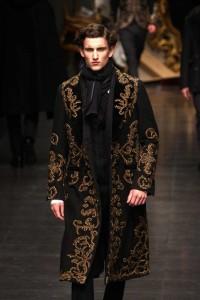 Nella foto, in alto: Defileé di moda, indossatore con soprabito damascato