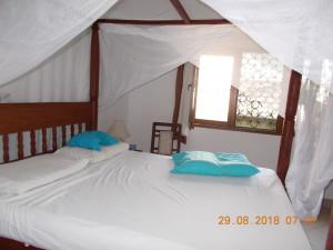 Nella foto, in alto: il letto a baldacchino con la zanzariera