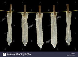 condoms-hanging-on-washing-line-against-a-black-background-AP5NMJ